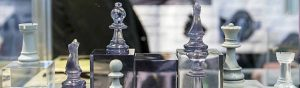 Chess pieces made out of composite materials are displayed in an arrangement of clear cubes.