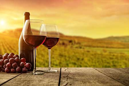 A pair of wine glasses and a bottle of wine rest on a table in a vineyard as the sun sets.