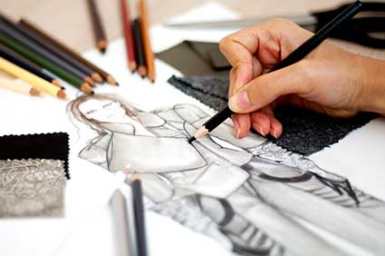 An artist sketches a new piece of fashion on a piece of paper.