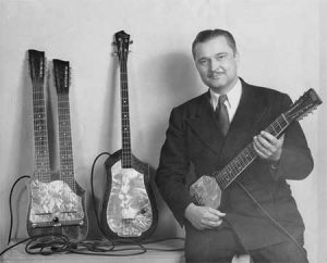 Seattle native Paul Tutmarc, poses with his invention, the Audiovox 736 Electric Bass guitar.
