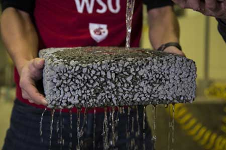 A researcher at Washington State University holds a sample of permeable, carbon fiber infused concrete that lets water drain naturally.