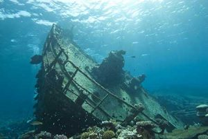 A shipwreck comes into view of a submersible sub.