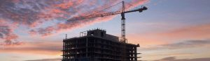 A construction crane looms over a new apartment building under construction in Washington.