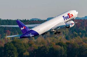 A Fed Ex freighter takes off from an airport.