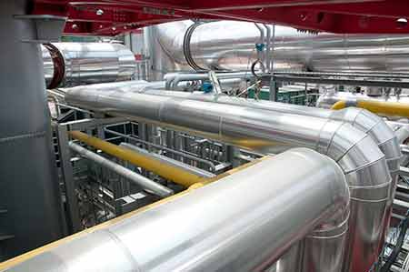 Interior of a pulp mill showing the network of pipes used to process raw materials into pulp.