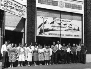 Employees pose in front of one of REI's original stores.