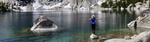 A hiker enjoys a crystal clear lake in the Cascade Mountains.