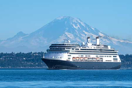 A cruise ship bound for Alaska leaves the Seattle waterfront. Mt. Rainier is in the background.