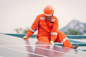 A workman installs solar panels.