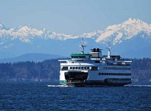 A Washington State ferry passes in front of the Olympic Mountains