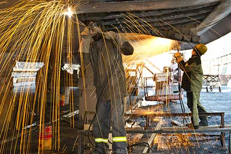 Welders work on a new boat in a shipyard, welding plates on the hull.