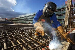 A welder reinforces rebar before concrete is poured onto a new foundation.