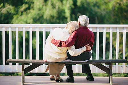 An elderly couple on a park bench enjoy their retirement years.