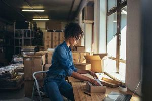 A small business owner prepares an ecommerce order for shipment.