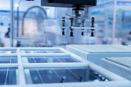 Robots assemble solar panels in a factory.